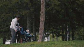 Família nova com uma criança que anda no parque vídeos de arquivo