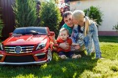 Família nova com uma criança que joga na grama fotografia de stock