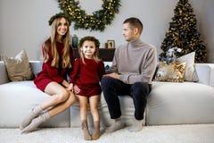 Família nova com uma filha no fundo de um Natal tr imagem de stock