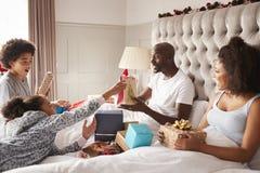 Família nova da raça misturada que senta-se na cama do ½ do ¿ do parentsï que dá-se presentes na manhã de Natal, fim acima fotografia de stock royalty free