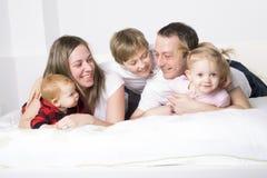 Família nova de cinco membros que tem o divertimento na cama Fotos de Stock Royalty Free