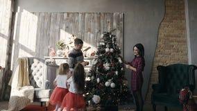 A família nova decora uma árvore de Natal Duas irmãs mais nova vestiram-se na mesma roupa corrida em torno de uma árvore de Natal video estoque