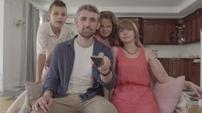 Família nova do retrato que olha a tevê em casa junto O pai guarda o telecontrole e comuta os canais, a esposa senta-se filme