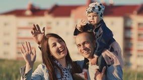 Família nova em um campo entre os spikelets verdes A filha senta-se no paizinho em ombros Acenam suas mãos pose video estoque