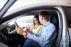 A família nova escolhe o carro novo em uma sala de exposições Esfera 3d diferente Fotografia de Stock Royalty Free