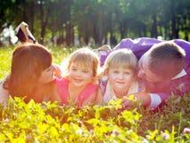Família nova feliz com as crianças que encontram-se na grama foto de stock