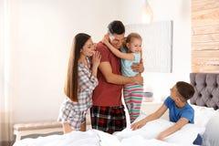 Família nova feliz com as crianças que têm o divertimento fotografia de stock