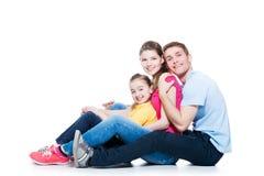 Família nova feliz com assento da criança Fotografia de Stock