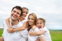 Família nova feliz com duas crianças Fotos de Stock
