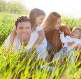 Família nova feliz com duas crianças Foto de Stock Royalty Free