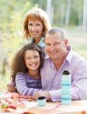 Família nova feliz com a filha no piquenique Fotografia de Stock