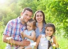Família nova feliz com a floresta das crianças na primavera Fotos de Stock