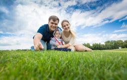 Família nova feliz com 9 meses de bebê idoso que relaxa na grama Fotografia de Stock Royalty Free