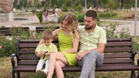Família nova feliz com seu filho que descansa no parque no verão em um banco filme