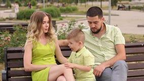 Família nova feliz com seu filho que descansa no parque no verão em um banco vídeos de arquivo