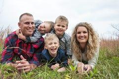 Família nova feliz com três rapazes pequenos Imagens de Stock