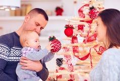 A família nova feliz decora a árvore de Natal do eco em casa Fotos de Stock