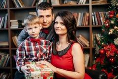 Família nova feliz em decorações do Natal fotografia de stock royalty free
