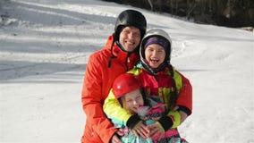Família nova feliz em Ski Suit With Funny Children na roupa brilhante do inverno Passeio guardando as mãos no parque maravilhoso filme