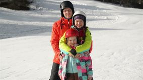 Família nova feliz em Ski Suit With Funny Children na roupa brilhante do inverno Passeio guardando as mãos no parque maravilhoso video estoque