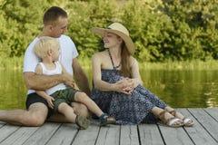 A família nova feliz, a mãe do pai e pouco filho louro estão sentando-se no cais do rio imagem de stock