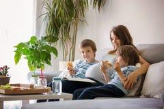 Família nova feliz, mãe grávida e dois meninos, comendo p saboroso foto de stock royalty free