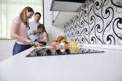 Família nova feliz na cozinha Fotografia de Stock