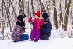 Família nova feliz na floresta do inverno fotografia de stock