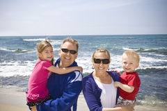 Família nova feliz na praia Foto de Stock Royalty Free