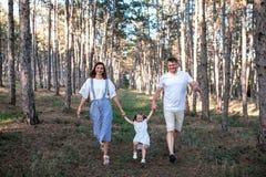 Família nova feliz que anda na floresta imagem de stock royalty free