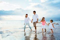 Família nova feliz que anda na praia Fotos de Stock Royalty Free