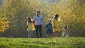 Família nova feliz que anda no parque do outono com seu cão pequeno video estoque