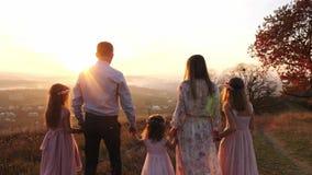 Família nova feliz que anda no parque do outono durante o por do sol Vista traseira vídeos de arquivo