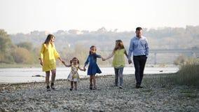Família nova feliz que anda pelo rio video estoque