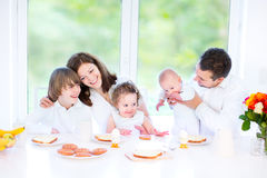 Família nova feliz que come o café da manhã do divertimento imagem de stock