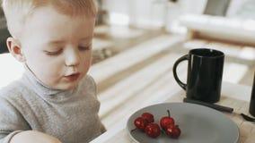 Família nova feliz que come o café da manhã na cozinha em feriados dentro vídeos de arquivo