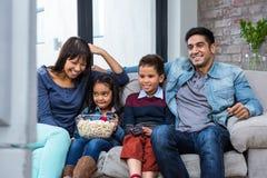 Família nova feliz que come a pipoca ao olhar a tevê fotografia de stock