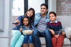 Família nova feliz que come a pipoca ao olhar a tevê Imagem de Stock Royalty Free