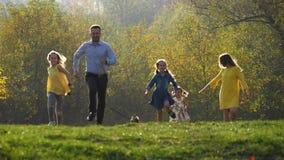 Família nova feliz que corre no parque do outono com seu cão pequeno filme