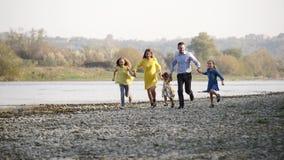 Família nova feliz que corre pelo rio video estoque