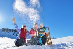 Família nova feliz que joga na neve fresca no dia de inverno ensolarado bonito exterior na natureza Imagem de Stock Royalty Free