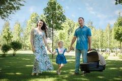 Família nova feliz que passa o tempo junto fora na natureza verde imagem de stock