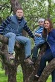 Família nova feliz que senta-se em uma árvore Imagens de Stock Royalty Free
