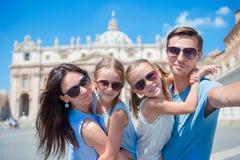 Família nova feliz que toma o selfie na igreja da basílica de St Peter na Cidade do Vaticano, Roma Pais e crianças felizes do cur fotografia de stock