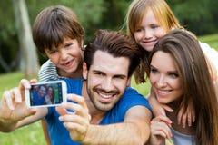 Família nova feliz que toma selfies com seu smartphone na paridade Fotografia de Stock Royalty Free