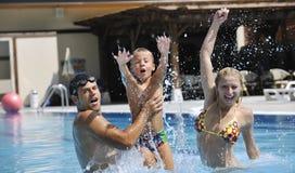 A família nova feliz tem o divertimento na piscina Imagens de Stock
