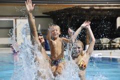 A família nova feliz tem o divertimento na piscina Fotografia de Stock