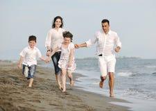 A família nova feliz tem o divertimento na praia Imagens de Stock