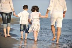 A família nova feliz tem o divertimento na praia no por do sol Fotografia de Stock