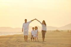 A família nova feliz tem o divertimento na praia no por do sol Imagens de Stock